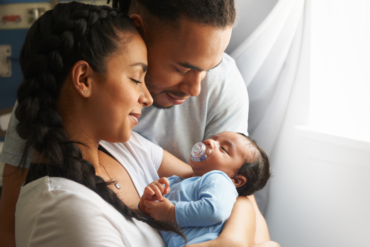 mom and dad looks lovingly at newborn baby
